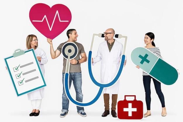 Persone felici che tengono le icone di assistenza sanitaria