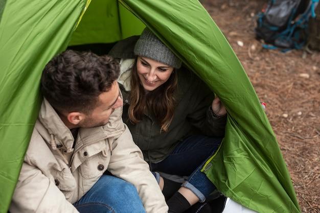 Persone felici del colpo medio che chiacchierano in tenda
