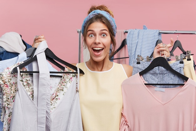 Persone, felicità, shopping, concetto di acquisto. bella donna che ha buon umore mentre tiene in mano molti appendini con i vestiti, provando gioia mentre attende con impazienza un nuovo acquisto o un vestito alla moda