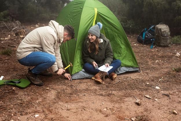 Persone full shot con mappa e tenda