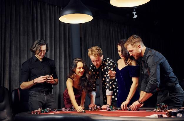 Persone in abiti eleganti in piedi e giocare a poker nel casinò insieme