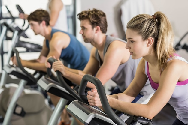 Persone in forma facendo cyclette in palestra