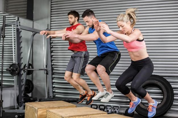 Persone in forma facendo esercizi con box in palestra crossfit