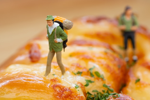 Persone in miniatura: backpackers walking on sausage bread.