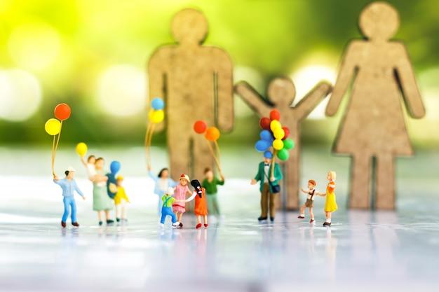 Persone in miniatura: bambini che giocano con il pallone.