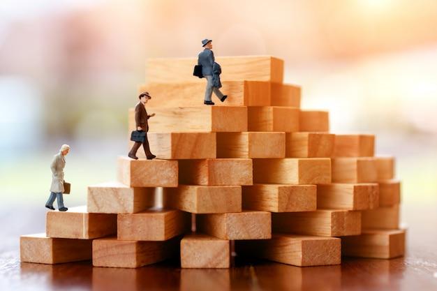Persone in miniatura che camminano sul gradino delle pile di blocchi di legno.