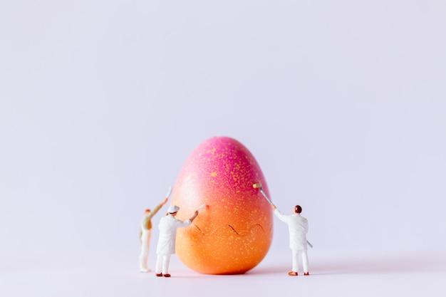 Persone in miniatura che dipingono le uova di pasqua per il giorno di pasqua