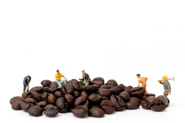 Persone in miniatura che lavorano con chicchi di caffè tostati