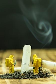 Persone in miniatura che lavorano con mozzicone di sigaretta e cenere close up.