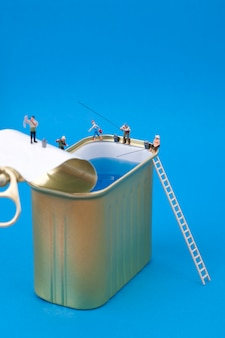 Persone in miniatura che pescano su lattine