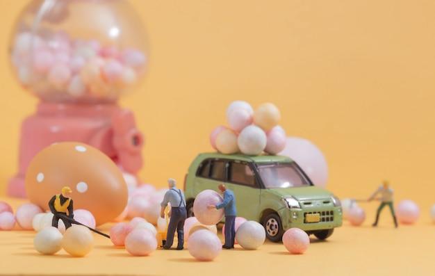 Persone (in miniatura) che preparano le vacanze di pasqua del distributore automatico di giocattoli egg. composizione di messa a fuoco selettiva e morbido colore pastello tonico