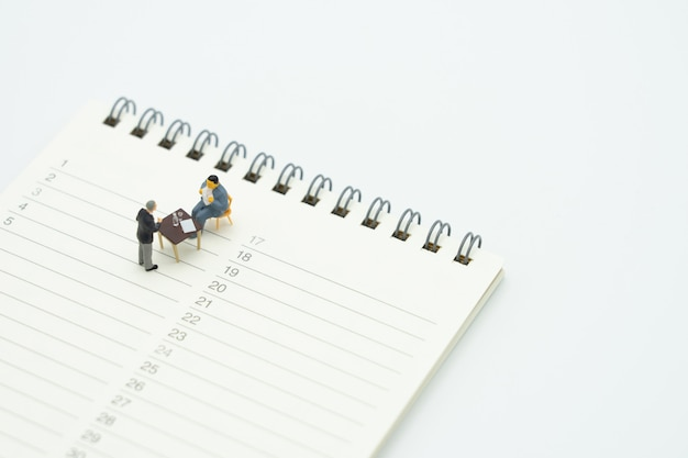 Persone in miniatura che siedono consulenza servizi di consulenza per pagare le tasse affari