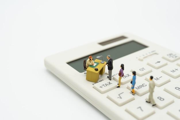 Persone in miniatura coda di retribuzione reddito annuale (iva) dell'anno calcolatrice.