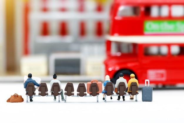 Persone in miniatura con bagagli in attesa di autobus. concetti di trasporto.