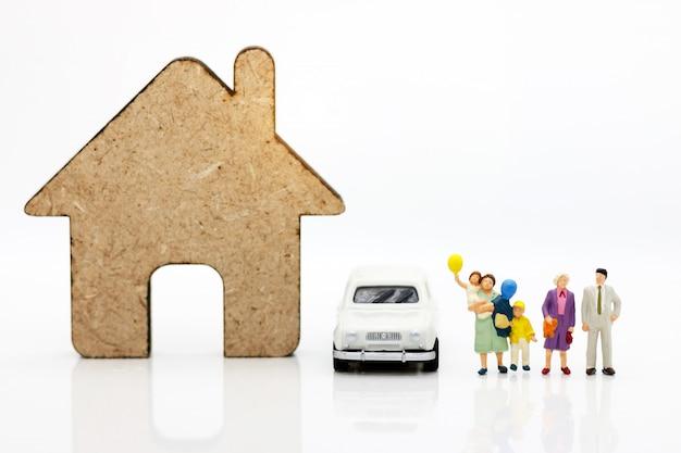 Persone in miniatura con la famiglia in piedi con case e auto.