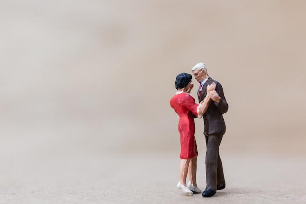 Persone in miniatura, coppia danza su fondo in legno