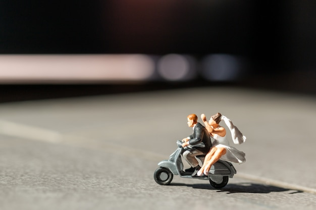 Persone in miniatura, coppia innamorata in sella a una moto