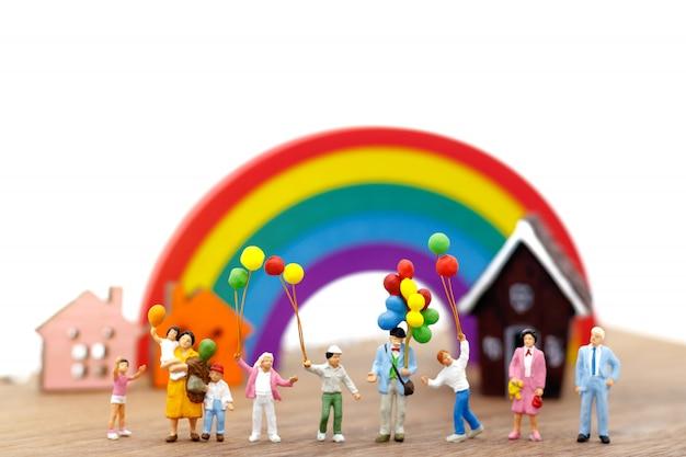 Persone in miniatura, famiglia e bambini si divertono con palloncini colorati.