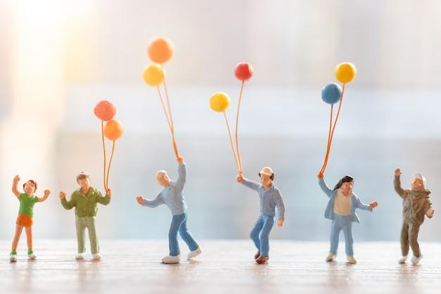 Persone in miniatura: famiglia felice che cammina con palloncini