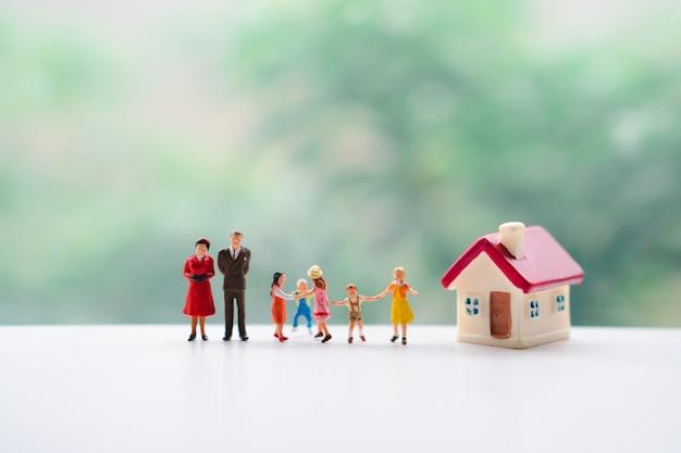 Persone in miniatura, famiglia felice che gioca insieme usando come concetto di famiglia