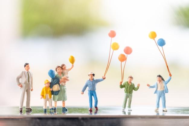 Persone in miniatura: famiglia felice con palloncini