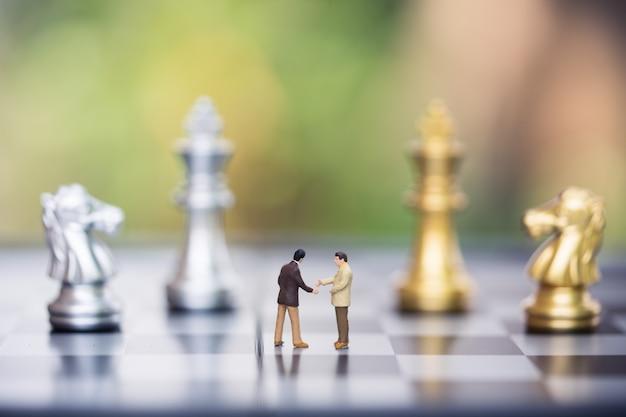Persone in miniatura: figura di piccolo imprenditore in piedi contro la parete della scacchiera con pezzi degli scacchi