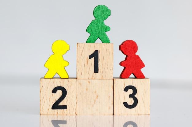 Persone in miniatura: figure colorate in piedi sul podio in legno 1,2,3.