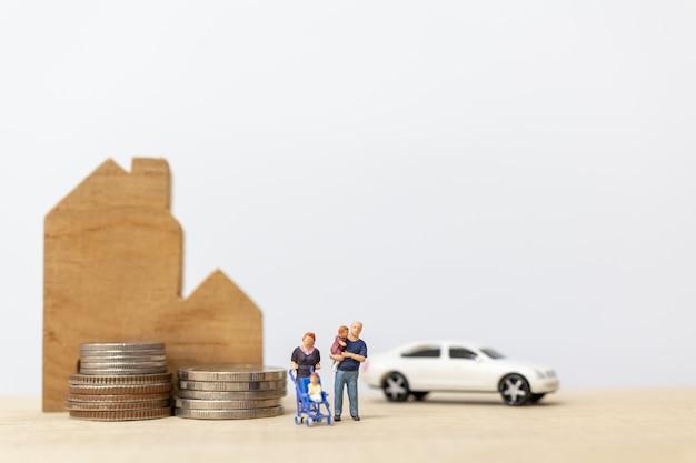 Persone in miniatura: genitori con bambini con casa e accatastamento di monete