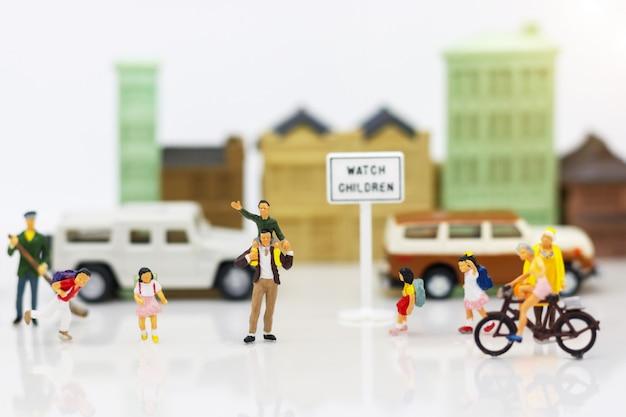 Persone in miniatura: genitori e figli in città.