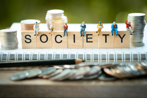 Persone in miniatura, gruppo di uomini d'affari seduti su blocchi di legno con la parola società.