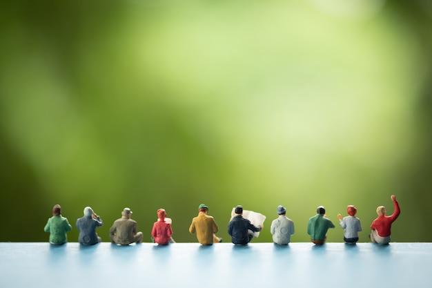 Persone in miniatura: gruppo di uomini d'affari seduti su un libro.