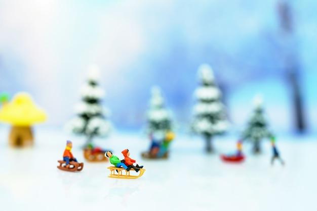 Persone in miniatura: i bambini giocano con il cursore della neve.