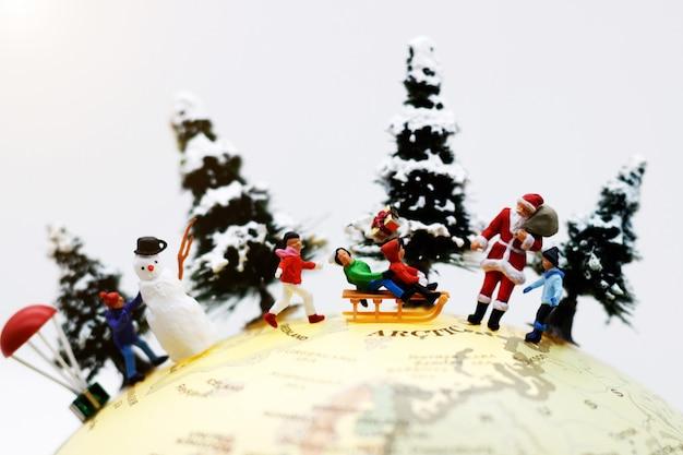 Persone in miniatura: i bambini si divertono con babbo natale e pupazzo di neve sul globo.