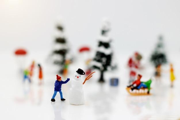Persone in miniatura: i bambini si divertono con il pupazzo di neve.
