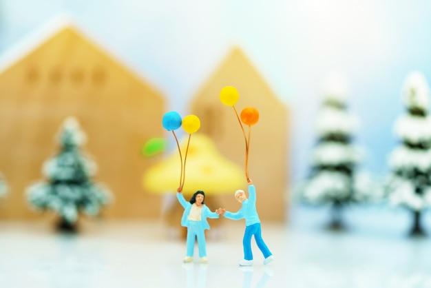 Persone in miniatura: i bambini si divertono con palloncini colorati prima dell'albero di natale.