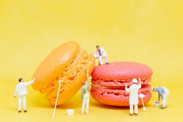 Persone in miniatura: i pittori colorano il macaroon