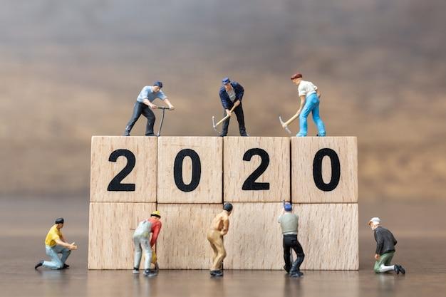 Persone in miniatura: il gruppo di lavoratori crea il blocco di legno numero 2020