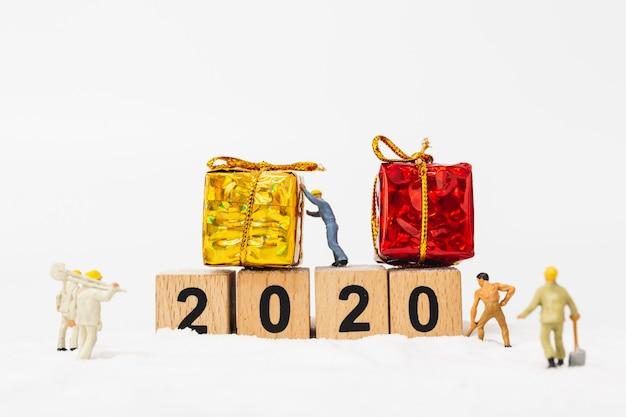 Persone in miniatura, il gruppo di lavoro crea il blocco di legno numero 2020