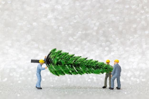 Persone in miniatura: il gruppo di lavoro prepara l'albero di natale