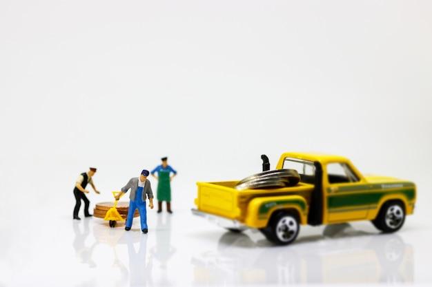 Persone in miniatura: il lavoratore sposta la pila di monete in macchina.