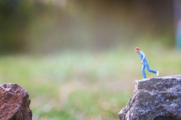 Persone in miniatura: in esecuzione su una roccia con sfondo di natura