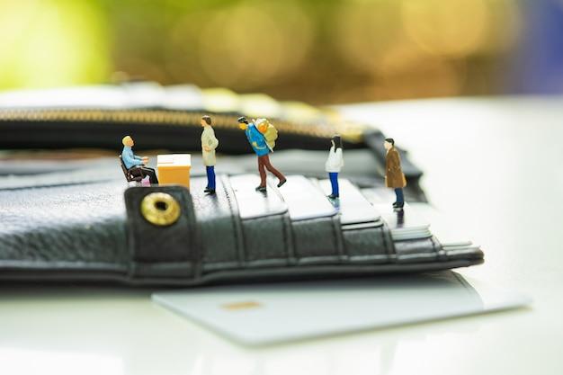 Persone in miniatura in fila allo sportello bancario sulla borsa piena di carta di credito.