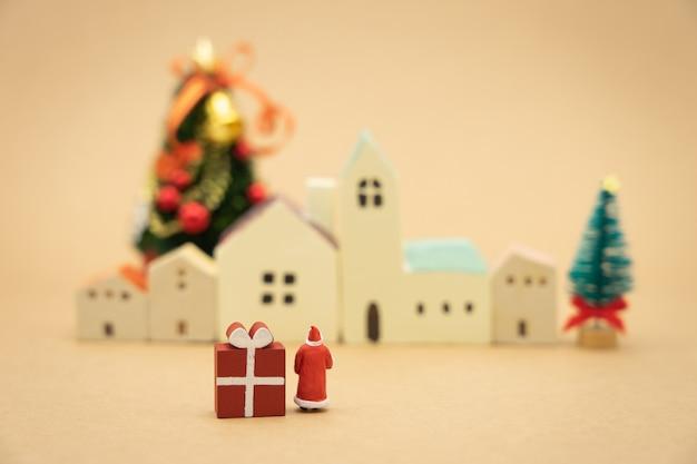 Persone in miniatura in piedi sull'albero di natale festeggia il natale il 25 dicembre