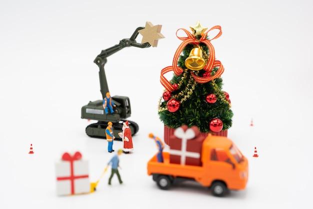 Persone in miniatura in piedi sull'albero di natale festeggia il natale o