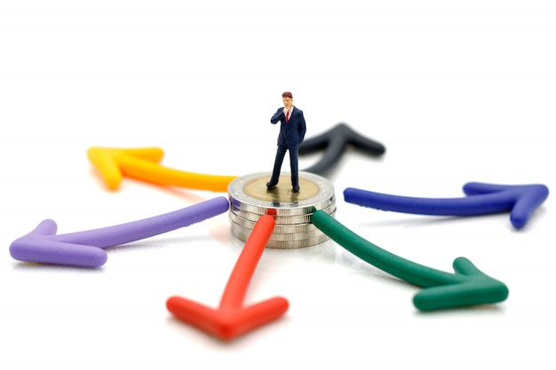 Persone in miniatura in piedi sulle monete con scelta di percorso freccia.