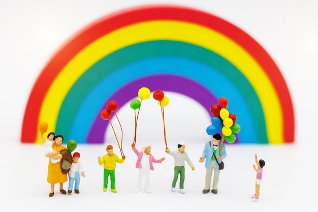 Persone in miniatura: la famiglia e i bambini si divertono con il palloncino colorato.