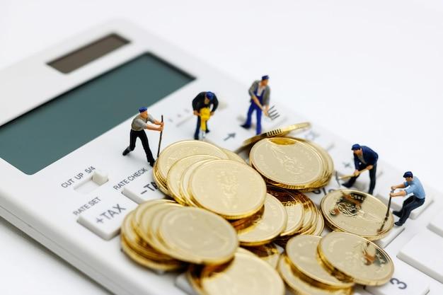 Persone in miniatura: lavoratori che lavorano su monete d'oro con calcolatrice.