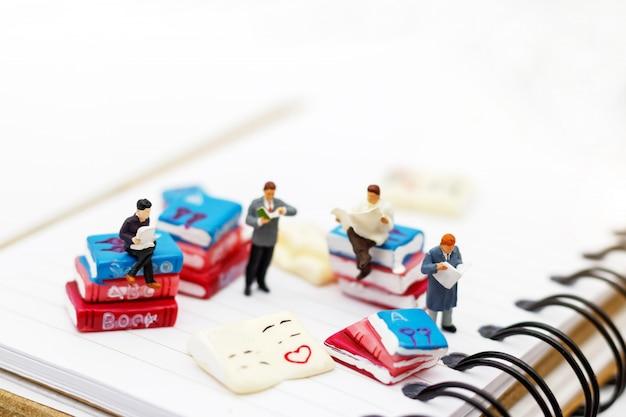Persone in miniatura: libro di lettura del team aziendale, concetto di educazione.