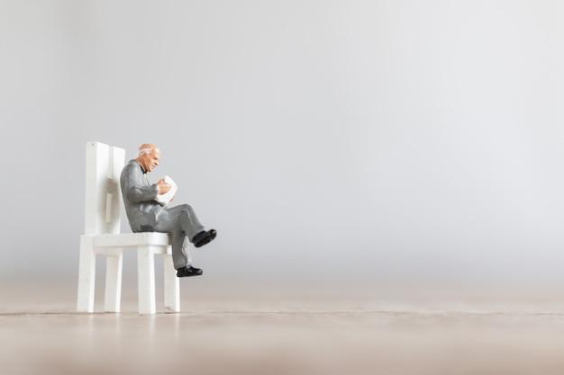 Persone in miniatura: libro di lettura dell'uomo d'affari sulla sedia