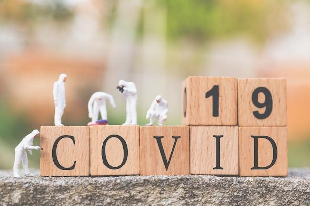 Persone in miniatura: medici con ispezione della tuta protettiva, diffusione o coronavirus, cov, concetto di epidemia di covid-19